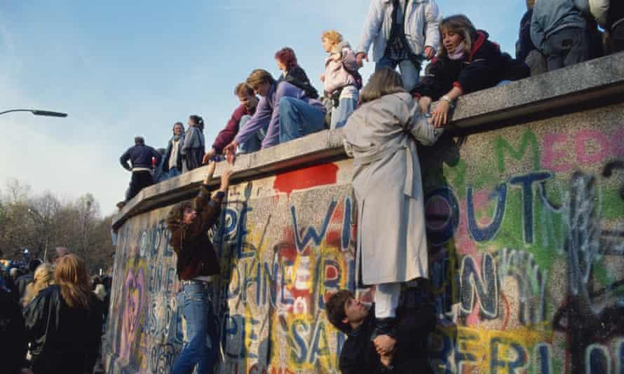 women climb the  Berlin Wall on November 10, 1989 in Berlin, Germany