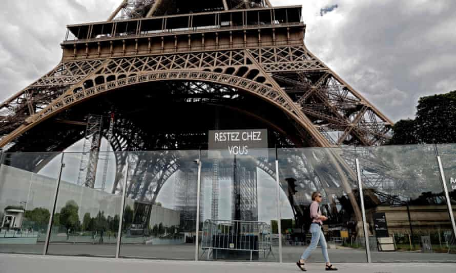 """A woman walks by the Eiffel Tower where a screen displays the words """"Stay at Home""""."""