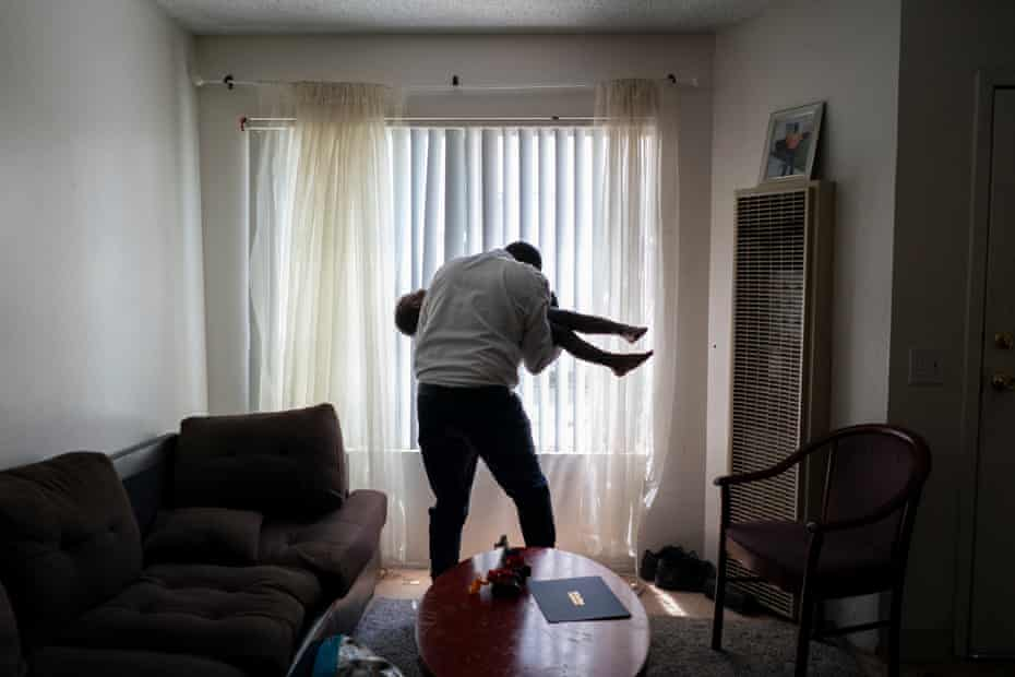 Okello plays with his son Ezekiel in their living room.