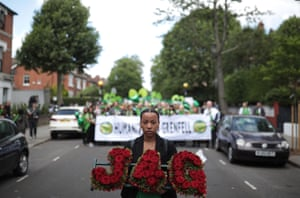 A woman holds a floral tribute of red roses spelling J4G (Justice4Grenfell ) as she walks to the Wall of Truth