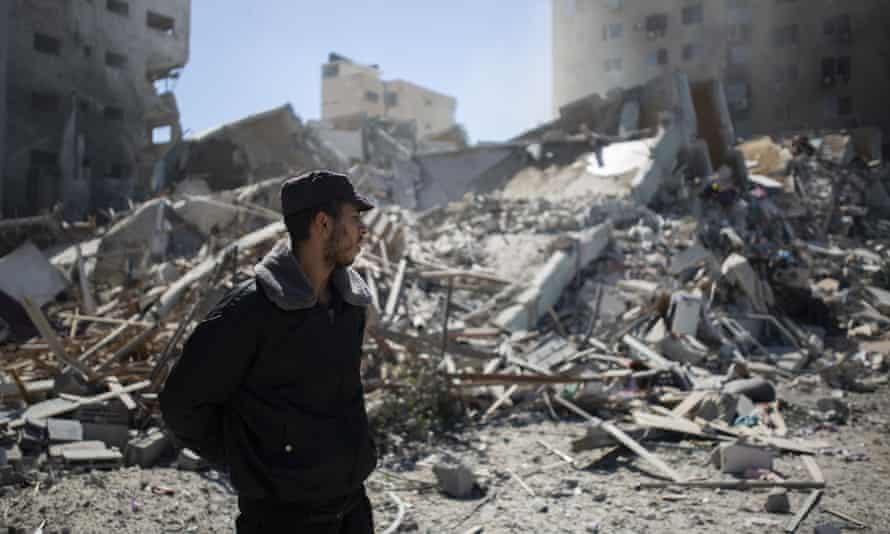 A Palestinian policeman stands in the rubble of a building destroyed by an Israeli airstrike that housed the Associated Press' offices in Gaza City.