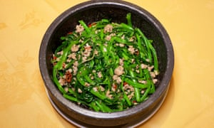 A thick round pot with morning glory, speckled with pieces of pork and chilli
