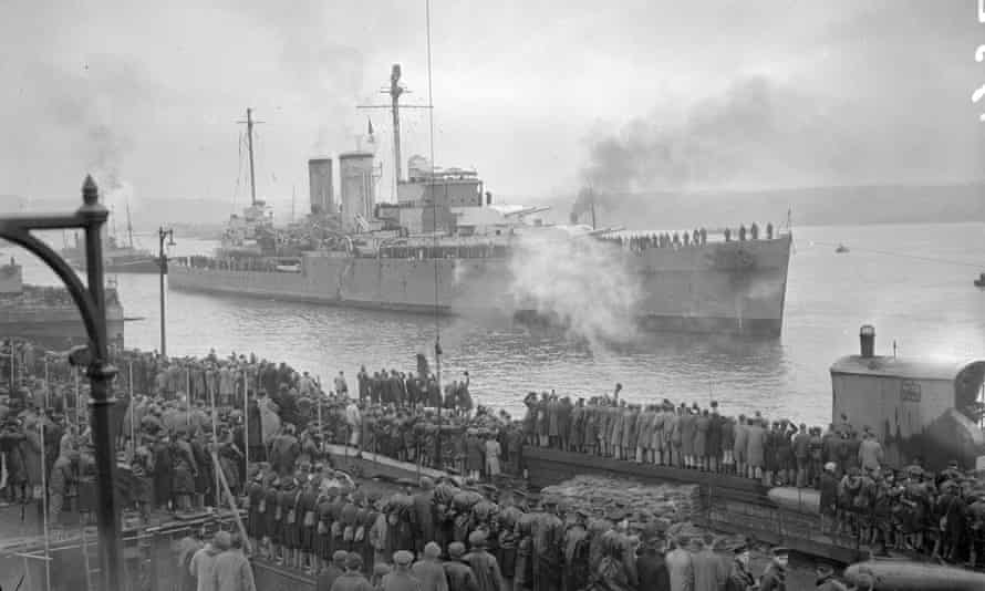 HMS Exeter coming alongside at Plymouth in February 1940 watched by a crowd.