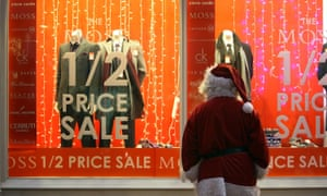 """A """"Father Christmas"""" looks in a menswear shop window display offering pre-Christmas reductions"""