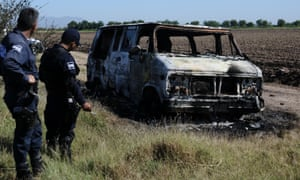 police investigate a burned out van in Mexico.
