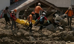 Rescuers carry away the body of a victim in Palu, Central Sulawesi, Indonesia, on Wednesday after last month's earthquake and tsunami.