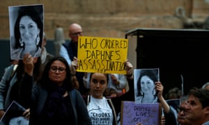 People hold up posters and pictures of anti-corruption journalist Daphne Caruana Galizia during a vigil and demonstration in May.