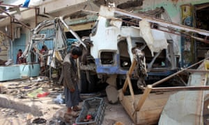 A Yemeni child next to a bus destroyed by a Saudi-led coalition airstrike in Dahyan, Yemen, August 2018