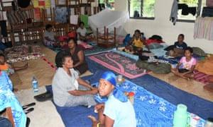 People take shelter inside an evacuation center in Suva, Fiji, before Cyclone Yasa.