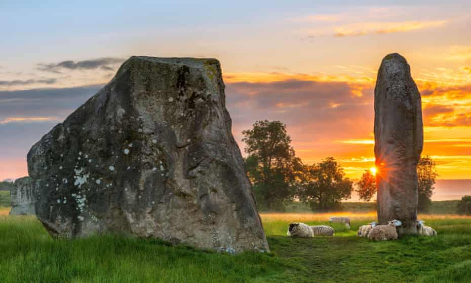 The sun melts away the dawn mist as it rises behind the ancient Sarsen Stones at Avebury in Wiltshire on a calm morning