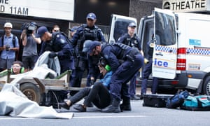 An Extinction Rebellion protester is placed under arrest by Queensland police in Brisbane