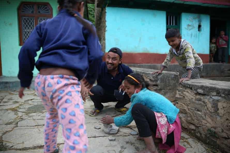 Prem Singh, a local activist, plays with children in Durmi village, near Pagna.