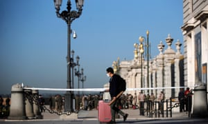 A man wearing protective mask pulls his suitcase in front of the Royal Palace in Madrid, Spain.