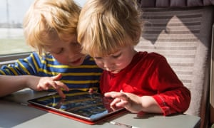 Two young boys playing on an iPad