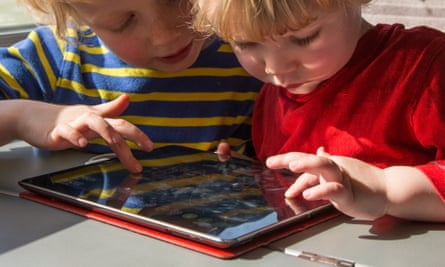 Two children playing on an iPad