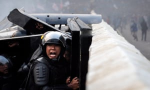 An Indonesian police officer shouts during a clash with protesters outside the parliament building in Jakarta.