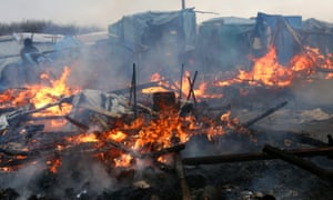 A hut burns as part of the 'Jungle' camp in Calais is cleared