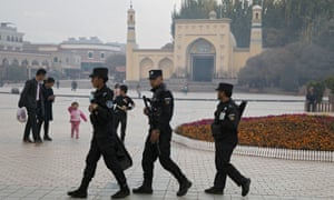 Uighur security personnel patrol near the Id Kah Mosque in Kashgar in western China's Xinjiang region. China has threatened to retaliate against the US's new Uighur human rights law.