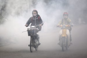 People ride through smoke plumes created by residents burning waste in the street. Recent reports reveal the air pollution rate in Hanoi has risen to at a hazardous level