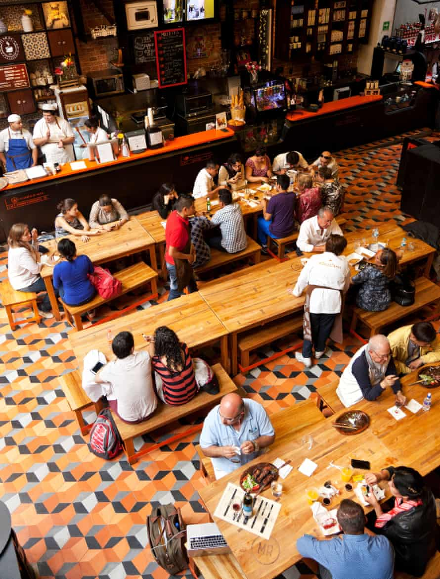 People sitting on benches at long tables in the Mercado Roma food hall.