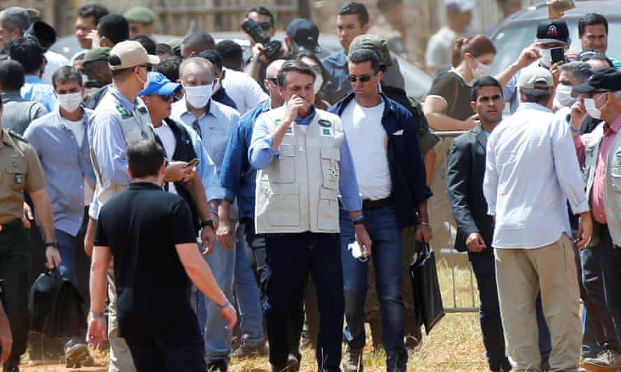 President Jair Bolsonaro dispenses with a mask and touches his face as he visits a temporary field hospital, amid the coronavirus outbreak, in Aguas Lindas, state of Goias,Brazil, at the weekend,