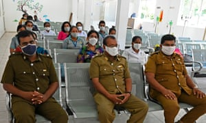 Sri Lankan public health officials and medical workers wearing facemasks wait for their turn to cast postal ballots for the parliamentary elections.