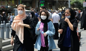 People walk along a street in Tehran as the government makes wearing masks mandatory in public, 5 July 2020.