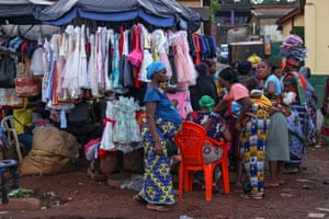 Conakry, Guinea. Women gather at a market stall in the city