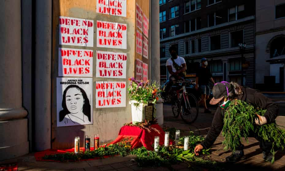 A demonstrator adds flora to a memorial for George Floyd and Breonna Taylor in Oakland.