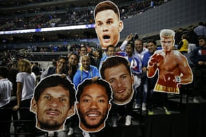 Fans hold cardboard heads of players from the Dallas Mavericks and Detroit Pistons (and Dolph Lundgren) at the end of their NBA basketball game