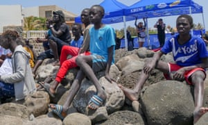 Senegalese boys and young men watch surfers tackle the Ngor Right