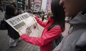 Tokyo commuters read an extra edition of a newspaper about Emperor Akihito's plans to abdicate in 2019.
