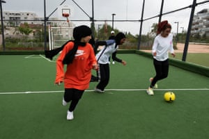 Girls train at a public football pitch in Montreuil, in the Paris suburbs