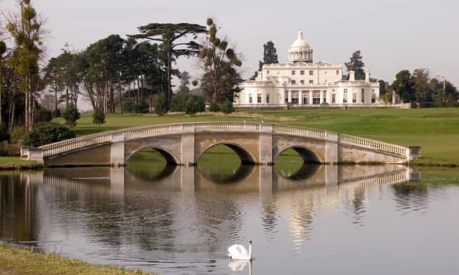 Stoke Park - imposing Georgian mansion set on a gentle slope above lake and decorative bridge