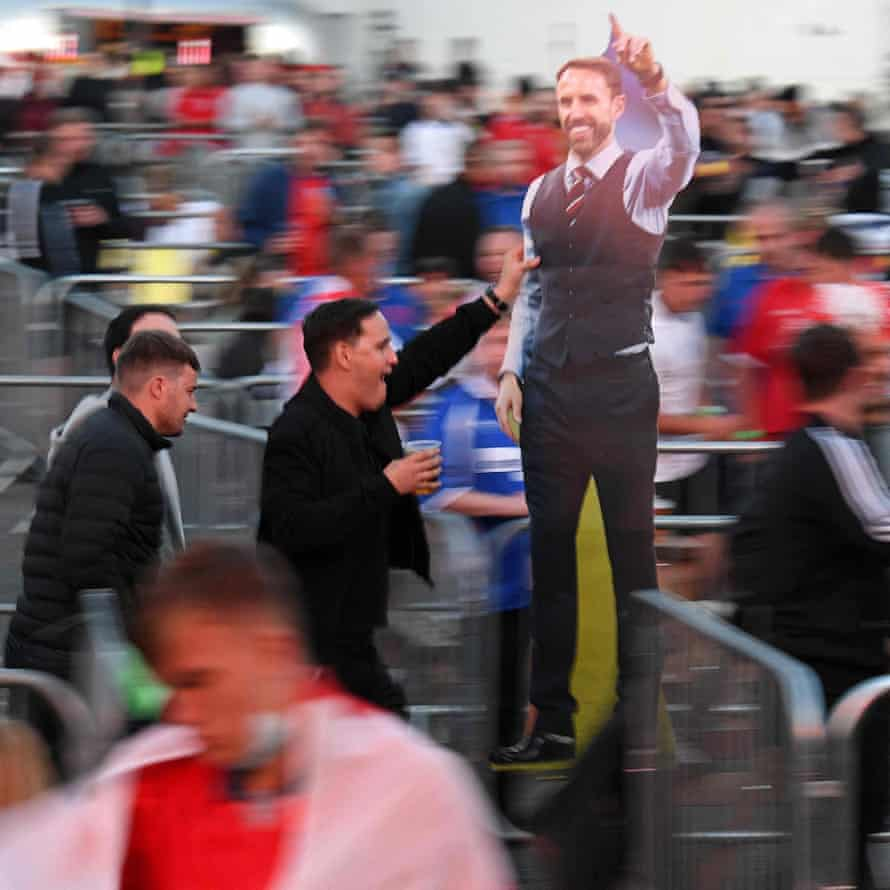 England fans carry a cardboard cut out of England manager Gareth Southgate at the Fan Park in Manchester.