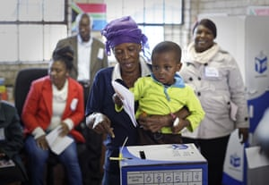 A voter lets her grandson cast the ballot in Soweto, Johannesburg