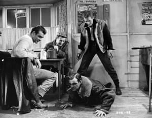 A scene from the film Hell Drivers in which Connery ('Johnny'), Patrick McGoohan ('Red') and Sid James ('Dusty') laugh at Stanley Baker ('Tom') as he struggles on the floor.