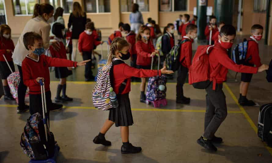 Children wait in a queue and social distance before entering a classroom in Pamplona, northern Spain.