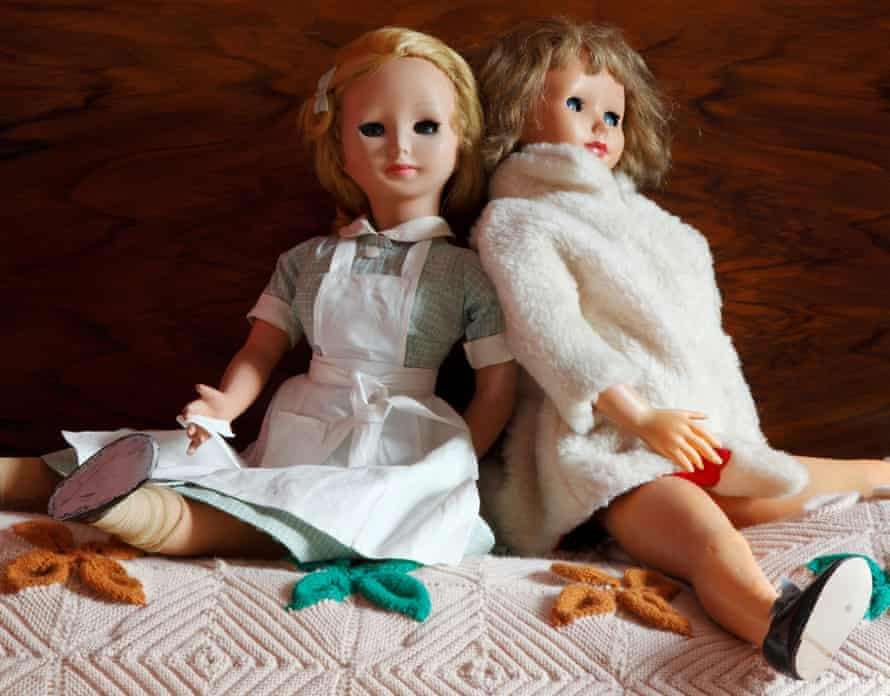 Two vintage dolls sitting up and leaning into each other on a bed.