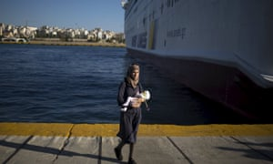 A migrant woman holds a child after arriving at the port of Piraeus near Athens.