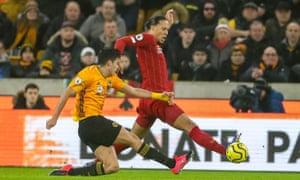 Liverpool's Virgil Van Dijk blocks a shot by Raul Jimenez.