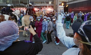 Medical workers pose for photographs as police officers and pedestrians cheer for them outside NYU Medical Center Thursday, 16 April 2020, in New York.