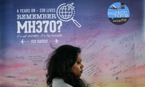 A woman walks past a banner bearing solidarity messages for passengers of the missing Malaysia Airlines flight MH370