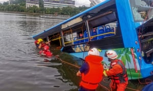 Rescue workers in hi-vis clothing pulling on ropes attached to a part-submerged bus