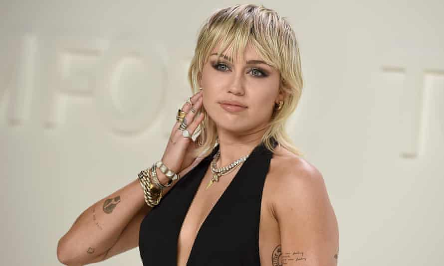 Miley Cyrus in evening wear at an event, with a shaggy blonde hairstyle falling just below the shoulders