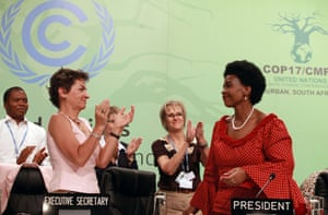 South African international relations minister, Maite Nkoana-Mashabane (right), receives a standing ovation from Figueres and hundreds of delegates at the closing session of the Durban climate talks in December 2011.