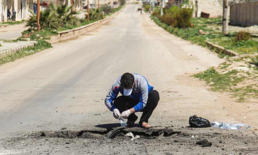 A Syrian man collects samples from the site of the attack in Khan Sheikhun in April.