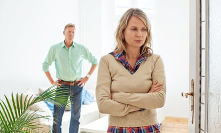 Mature couple having relationship difficultiesAnnoyed woman with her husband standing in background at home. Mature couple having relationship conflict.