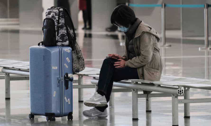 A passenger wears a protective face mask at an airport.