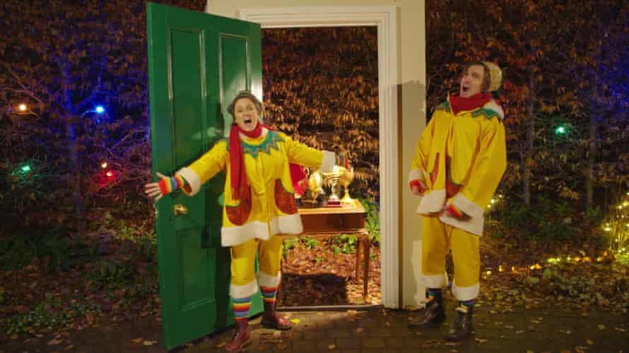 elves Barbara Hockaday and Ali Watt step through an advent calendar door.